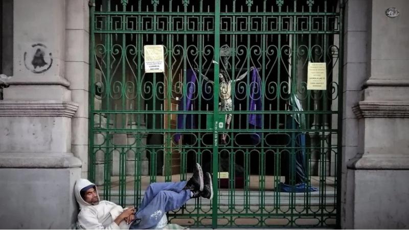 Un pobre junto a una iglesia cerrada en Argentina